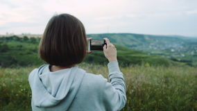 A mulher toma uma paisagem bonita em telefones da câmera video estoque