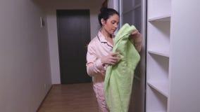 A mulher toma uma toalha do armário vídeos de arquivo