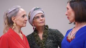 Mulher três adulta que fala sobre algo quando reunião amigável Amigos felizes da mulher que bisbilhotam no encontro f?mea vídeos de arquivo