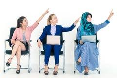 Mulher três caucasiano asiática muçulmana diversa que aponta acima imagens de stock royalty free