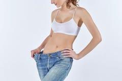 A mulher transformou-se calças de brim velhas magros e vestindo Imagem de Stock
