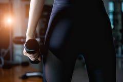 Mulher traseira feliz que dá certo com pesos no gym Fotografia de Stock