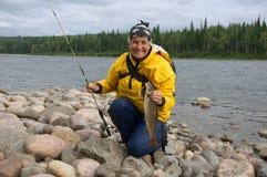 A mulher travou um lenok grande no rio Siberian selvagem Foto de Stock Royalty Free