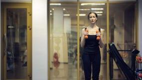 A mulher treina a ocupa com pesos na frente da câmera dentro do gym vídeos de arquivo