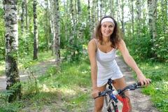 Mulher triguenha ativa na bicicleta vermelha Foto de Stock Royalty Free