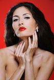 A mulher triguenha atrativa com cabelo magnífico toca em seu pescoço fotografia de stock royalty free