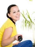 Mulher triguenha de sorriso que presta atenção à tevê Imagem de Stock