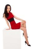 Mulher triguenha fina bonita no vestido vermelho que senta-se no cubo Fotografia de Stock