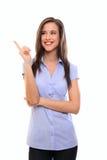 Mulher triguenha nova de sorriso que aponta no copyspace Imagens de Stock