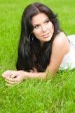 Mulher triguenha nova em um gramado foto de stock