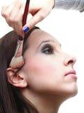 Mulher triguenha nova que aplica o pó com uma escova Imagem de Stock Royalty Free