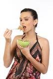 mulher triguenha nova que come macarronetes foto de stock