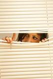 Mulher triguenha nova que olha através das cortinas fotografia de stock royalty free