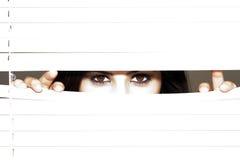 Mulher triguenha nova que olha através das cortinas Fotos de Stock Royalty Free