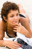 Mulher triguenha que encontra-se em uma areia Imagens de Stock Royalty Free