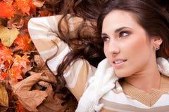 Mulher triguenha que encontra-se nas folhas de outono Imagens de Stock Royalty Free