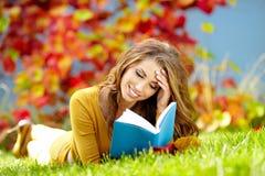 Mulher triguenha que lê um livro Fotos de Stock Royalty Free