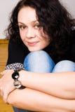 Mulher triguenha que senta-se em um assoalho de madeira imagem de stock royalty free