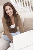 Mulher triguenha que usa o computador portátil em casa Imagem de Stock Royalty Free