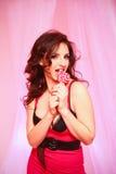 Mulher triguenha sedutor com um pirulito no fundo cor-de-rosa Foto de Stock