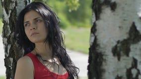 A mulher triste após relacionamentos quebrados, apenas no parque sob a árvore olha afastado lenta video estoque
