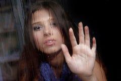 Mulher triste atrás do indicador molhado Imagens de Stock
