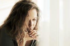 Mulher triste com os cabelos encaracolado longos que olham para baixo Imagem de Stock Royalty Free
