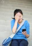 Mulher triste com telefone celular fotografia de stock royalty free