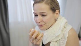 A mulher triste cura um nariz ralo com uma cebola, espirra alto e limpa seu nariz vídeos de arquivo
