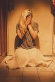 Mulher triste, deprimida e só que senta-se em telhas de assoalho, em uma saia, com os pés descalços Fotos de Stock Royalty Free