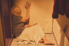 Mulher triste, deprimida e só que senta-se em telhas de assoalho, em uma saia, com os pés descalços Foto de Stock