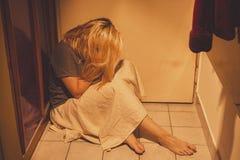 Mulher triste, deprimida e só que senta-se em telhas de assoalho, em uma saia, com os pés descalços Imagem de Stock