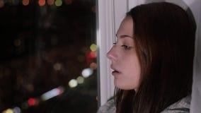 A mulher triste do ruivo senta-se no peitoril e no grito da janela video estoque