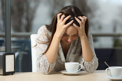 Mulher triste e deprimida apenas em uma cafetaria foto de stock