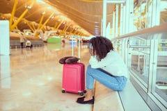 Mulher triste e infeliz no aeroporto com o voo cancelado imagens de stock royalty free