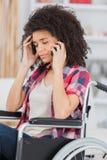 Mulher triste na cadeira de rodas no telefone Fotografia de Stock