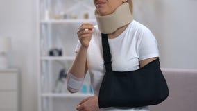 Mulher triste no estilingue do braço e no telefone de fala do colar cervical, dor de pescoço de sentimento vídeos de arquivo
