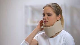 Mulher triste no telefone de fala do colar cervical da espuma que sente de repente a dor de pescoço afiada vídeos de arquivo