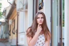 Mulher triste pensativa que senta apenas fora a vista a tomar partido imagens de stock