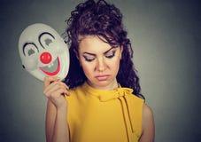 Mulher triste que descola a máscara do palhaço que expressa a alegria foto de stock royalty free