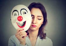 Mulher triste que descola a máscara feliz do palhaço foto de stock
