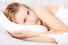 Mulher triste que encontra-se na cama Imagem de Stock Royalty Free