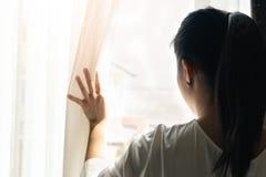 Mulher triste que mantém as cortinas abertas para olhar em casa fora de uma grande janela clara, interior imagens de stock