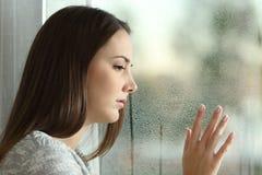 Mulher triste que olha a chuva através de uma janela foto de stock