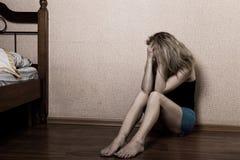 Mulher triste que senta-se apenas em uma sala vazia ao lado da cama Violência doméstica imagens de stock