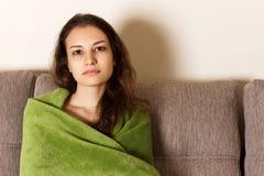 Mulher triste que senta-se no sofá em casa a menina cansado no sofá é coberta com uma cobertura fotos de stock royalty free