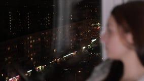 A mulher triste senta-se no peitoril da janela, olhar na cidade da noite vídeos de arquivo
