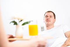 A mulher trouxe seu café da manhã do noivo na cama Imagem de Stock Royalty Free