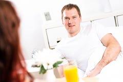 A mulher trouxe seu café da manhã do noivo na cama Fotografia de Stock Royalty Free
