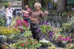 A mulher ucraniana vende flores no mercado local no centro de Lviv, Ucrânia Imagem de Stock